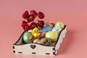 Easter eggs in a natural nest on a wooden tray, flowers and a decorative chicken on a pink background photo