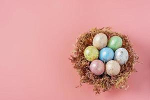 Easter eggs in a natural nest with moss on a pink background. View from above photo