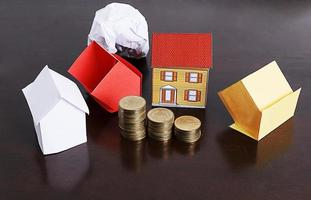 Mortgage loans concept with paper house and coins stack on wooden table photo