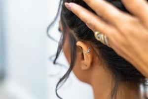 chica con piercing de oreja y mano de esteticista foto
