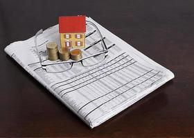 Paper house with coins stack and eyeglasses on news paper photo