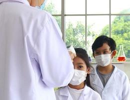 El maestro apuntó un termómetro de pistola electrónico a su frente para medir la temperatura corporal de los estudiantes. foto