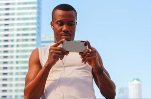 Hombres guapos en ropa deportiva relajándose del ejercicio al aire libre escuchando música desde un teléfono inteligente o teléfono móvil conceptos de ejercicio saludable foto