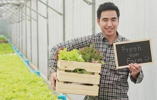 Asian man holding a basket of fresh vegetables and organic vegetables from the farm Vegetable cultivation and hydroponics Health concept for agriculture photo
