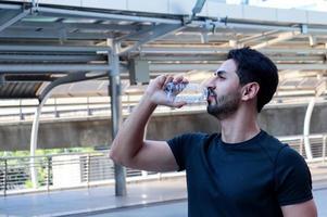 Hombres guapos en ropa deportiva bebiendo agua de botellas de plástico después de hacer ejercicio al aire libre foto