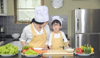 Asian woman young mother with son boy cooking salad food with vegetable holding tomatoes and carrots, bell peppers on plate for happy family cook food enjoyment lifestyle kitchen in home photo