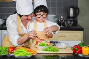 Asian woman young mother with son boy cooking salad mom sliced vegetables food son tasting salad dressing vegetable carrots and tomatoes bell peppers happy family cook food enjoyment lifestyle kitchen photo