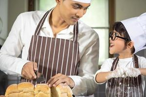 Asian Boy wear glasses Tease dad cooking with white flour Kneading bread dough teaches children practice baking ingredients bread, egg on tableware in kitchen lifestyle happy Learning life with family photo