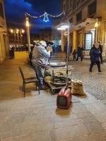 Hombre vendiendo castañas cocidas al público en el centro de la ciudad. foto