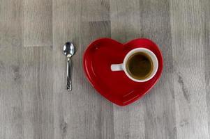 una taza de café con un platillo en forma de corazón foto