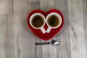 dos tazas pequeñas de café con un platillo de corazón foto