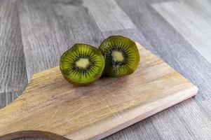 Composición con kiwi y una tabla de cortar de madera. foto
