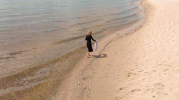 en ung kvinna i en klänning springer längs stranden antenn skjuta video