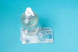 Container with gel alcohol and brazilian real money, on the light blue background photo