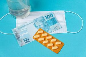Alcohol gel container, surgical mask, medicine and brazilian real money, on the light blue background photo
