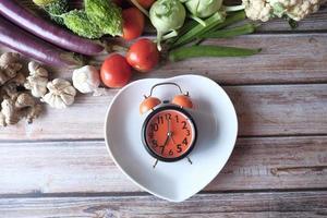 Selección de alimentos saludables con verduras frescas y reloj despertador en la placa foto