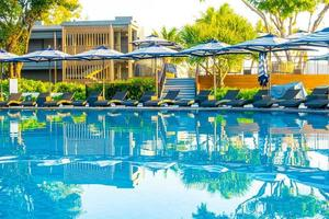 Umbrella and pool bed around outdoor swimming pool in hotel resort for travel holiday vacation photo