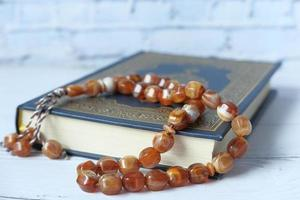 libro sagrado Corán y Rosario en la mesa, de cerca. foto