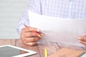 Mano de hombre con lápiz analizando gráfico de barras en papel foto