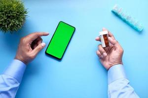 Top view of young man hand using smart phone and holding a pill container photo