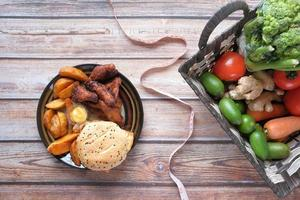 Junk food, fresh vegetables and measuring tape on wooden table photo