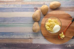 Vista superior de la rodaja de patata cruda y huevo en un recipiente foto
