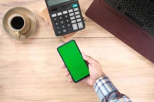 Top view of man hand using smart phone on office desk photo