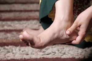 Close up on women feet and hand massage on injury spot. photo