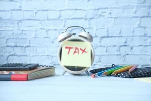 palabra de impuestos en el despertador con papelería en la mesa. foto