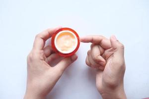 Woman applying beauty cream onto skin at home top view photo
