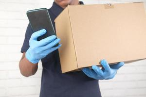 Delivery man hand in latex gloves holding smart phone and card box photo