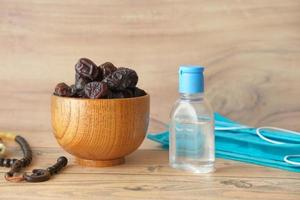 fruta fresca de dátiles en un tazón, rosario de oración, desinfectante de manos y mascarilla en la mesa foto