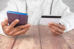 Senior women hand holding credit card and using smart phone shopping online photo