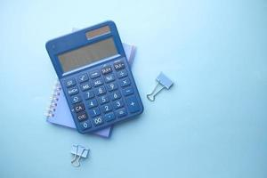 Close up of blue calculator and notepad on color background photo