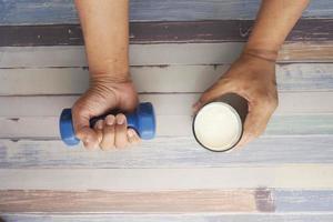 Mano de hombre joven haciendo ejercicio con pesas y sosteniendo un vaso de leche foto