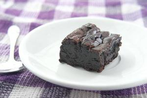 Slice of homemade brownie on plate on table photo