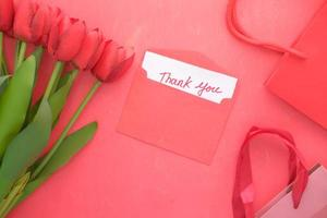 Thank you message on paper with tulip flower on red background photo