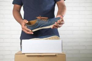 Young man open a box for shoes photo