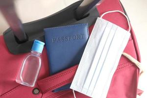 pasaporte, desinfectante de manos y mascarilla en la maleta en el suelo foto