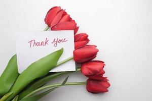Thank you message on paper with tulip flower on white background photo