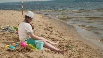 flicka som bygger ett slott av sand på flodstranden video