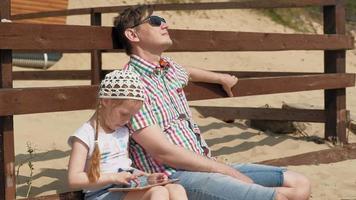 pai e filha estão usando um tablet de computador na praia video