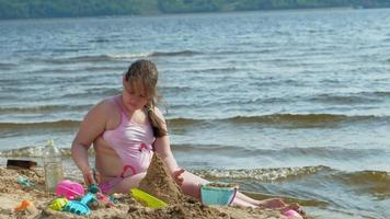flickan bygger ett slott av sand på flodstranden video
