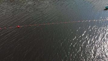 Orange buoys of safety on the river fencing of the place of swimming on the beach Aerial shooting video
