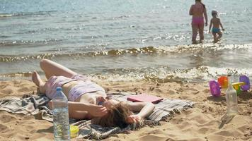 Young woman lying on the beach video
