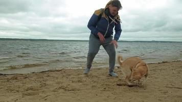 en man leker med en hund vid floden video