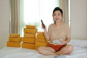 retrato, asia, mujer joven, está sentado, en la cama, tenencia, dinero, papel moneda, 100 usd, teléfono, con, el, teléfono, en, ella, habitación foto