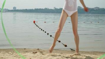 gymnaste de jeune femme vêtue d'un body blanc sur une plage de sable, dansant avec un ruban de gymnastique. video