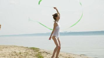 Young woman gymnast wearing a white bodysuit on a sandy beach, dancing with gymnastic ribbon. video