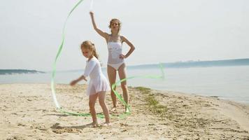 mère et fille en maillot de bain blanc dansant avec un ruban de gymnastique sur une plage de sable. video